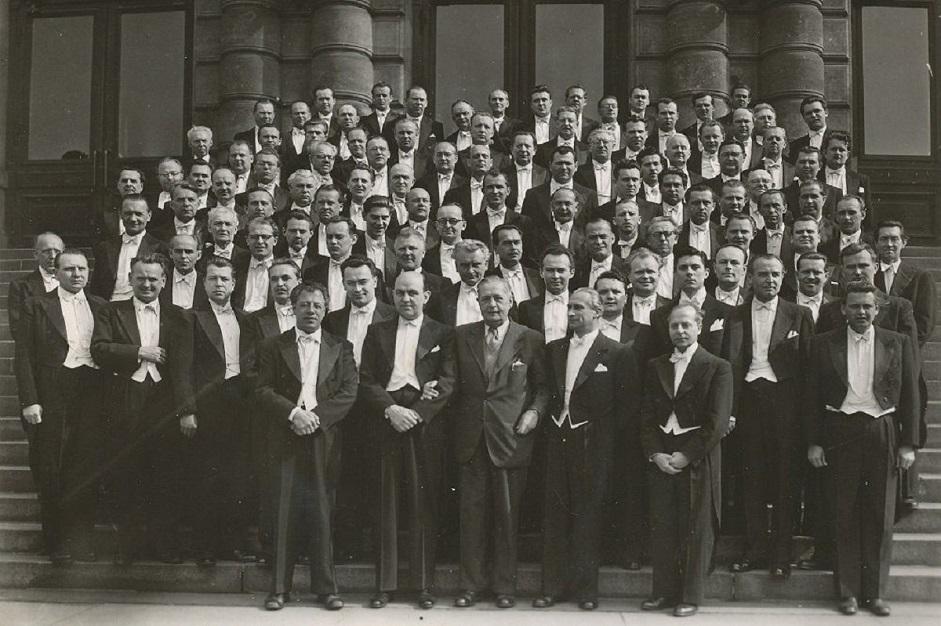 Skupinová fotografie České filharmonie na schodech Rudolfina (1954). Karel Ančerl v dolní řadě